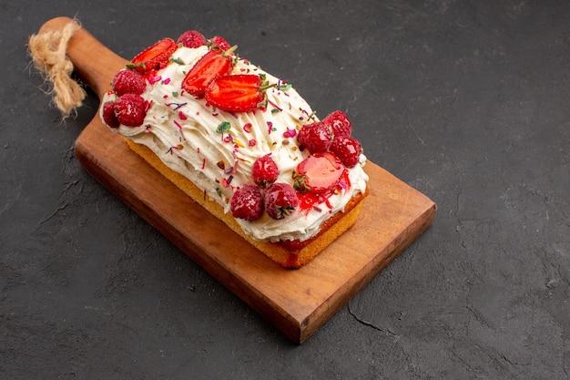 暗い背景の上のビューおいしいフルーツケーキキャンディーケーキビスケット生地フルーツ甘いパイ