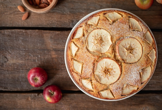 Top view of delicious fruit cake with apples and almonds on a dark wooden