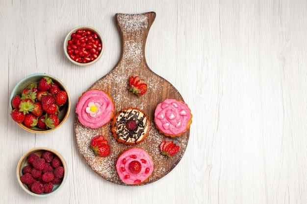 Vista dall'alto deliziose torte alla frutta dolci cremosi con frutti di bosco e frutta su sfondo bianco crema di tè dolce biscotto torta di dessert