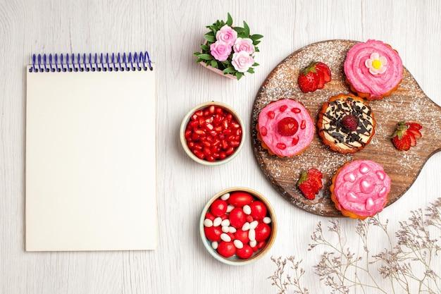 Вид сверху вкусные фруктовые торты сливочные десерты с конфетами и фруктами на белом фоне крем сладкое печенье десерт торт чай