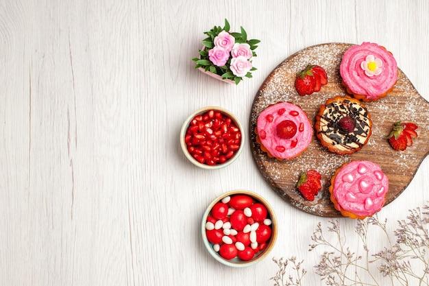 Vista dall'alto deliziose torte alla frutta dolci cremosi con caramelle e frutta su sfondo bianco crema biscotto dolce dessert torta tè