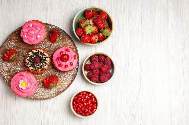 Вид сверху вкусные фруктовые пирожные, сливочные десерты с фруктами и ягодами на белом фоне, крем-чай, сладкий торт, печенье, десерт