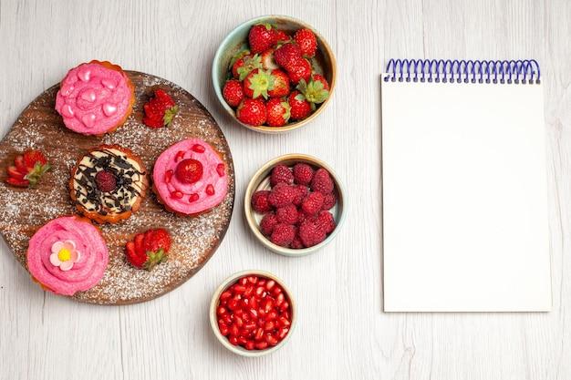 Vista dall'alto deliziose torte alla frutta dolci cremosi con frutta e bacche su sfondo bianco crema tè dolce torta biscotto dessert