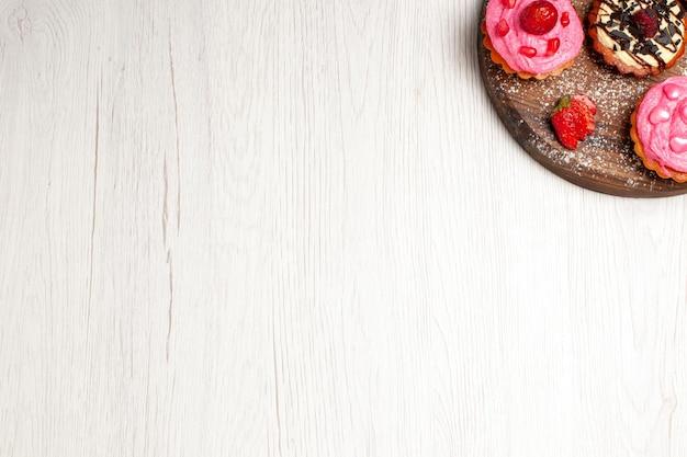 Vista dall'alto deliziose torte alla frutta dolci cremosi con frutta su sfondo bianco chiaro crema tè dessert biscotto torta biscotto