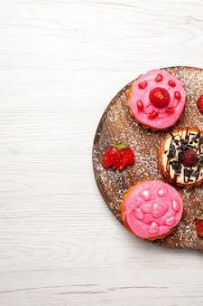 トップビューおいしいフルーツケーキクリーミーなデザートライトホワイトの背景にフルーツクリームティーデザートビスケットケーキクッキー
