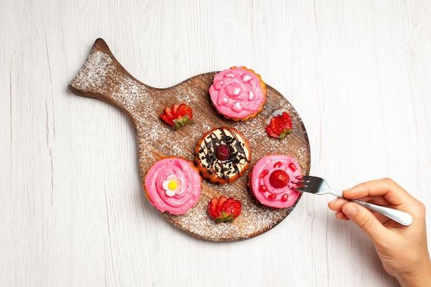 トップビューおいしいフルーツケーキクリーミーなデザートライトホワイトの背景にフルーツクリームティー甘いデザートケーキクッキー