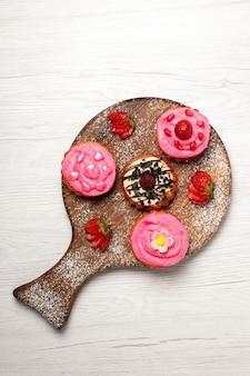トップビューおいしいフルーツケーキクリーミーなデザートとフルーツの白い背景クリームティーデザートビスケットケーキクッキー