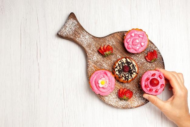 トップビューおいしいフルーツケーキクリーミーなデザートとフルーツの白い背景クリームティー甘いデザートケーキクッキー
