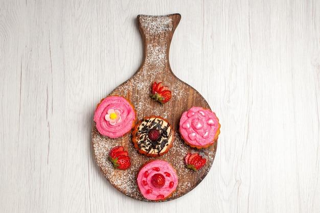 Vista dall'alto deliziose torte di frutta dolci cremosi con frutta su sfondo bianco crema di tè dolce biscotto dolce torta di dessert