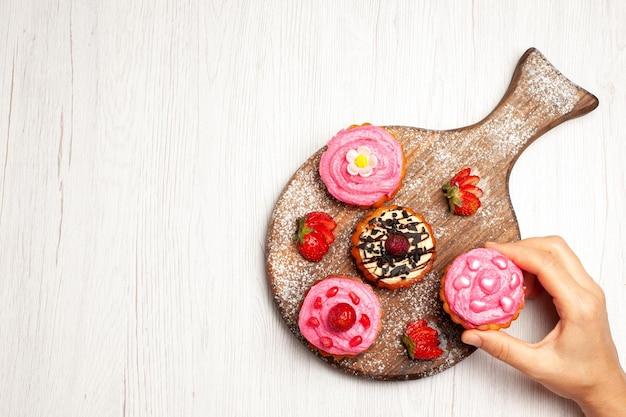 Vista dall'alto deliziose torte alla frutta dolci cremosi con frutta su sfondo bianco crema di tè dolce da dessert torta biscotto