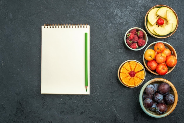 Top view delicious fruit composition fresh fruits on a dark background ripe fresh health diet fruit mellow