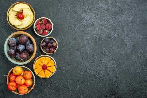 Vista dall'alto composizione di frutta deliziosa frutta fresca all'interno di piatti su sfondo scuro dieta fresca e matura frutta dolce