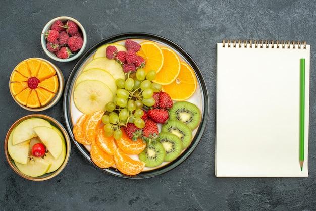 上面図おいしい果物の組成暗い背景に新鮮なスライスされたまろやかな果物熟した新鮮な健康果物まろやか