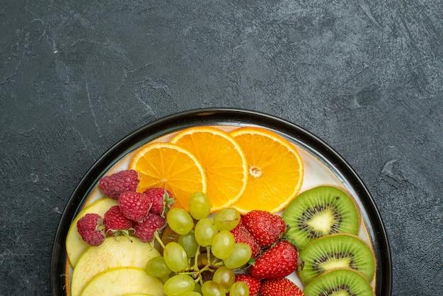 トップビューおいしい果物の組成暗い床に新鮮なスライスされたまろやかな果物熟した新鮮なまろやかな健康ダイエット
