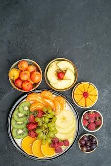 Vista dall'alto deliziosa composizione di frutta frutta fresca e affettata sullo sfondo scuro frutta fresca matura per la salute dolce