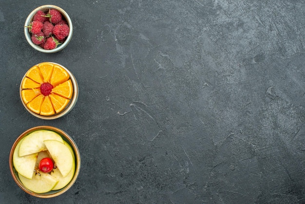 Top view delicious fruit composition fresh sliced and mellow fruits on a dark background ripe fresh health diet fruit mellow