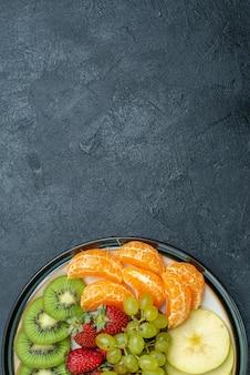 Vista dall'alto deliziosa composizione di frutta fresca affettata e frutta dolce sullo sfondo scuro dieta salutare fresca e matura