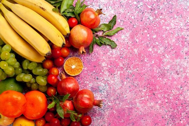 淡いピンクの机の上のビューおいしい果物の組成物