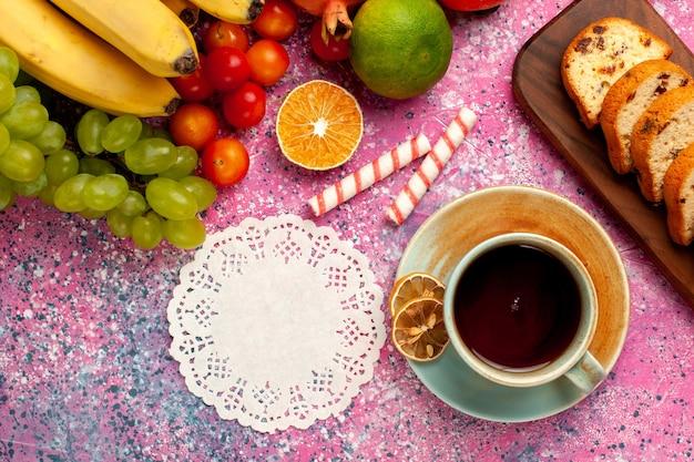 Vista dall'alto deliziosa composizione di frutta con torte a fette e tazza di tè sulla scrivania rosa chiaro