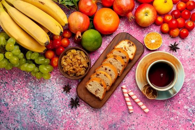 Vista dall'alto deliziosa composizione di frutta con torte a fette e tazza di tè sulla scrivania rosa