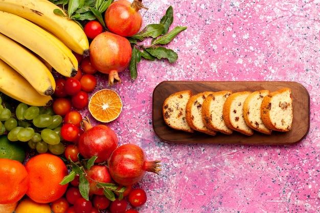 淡いピンクの机の上にスライスしたケーキとトップビューのおいしい果物の組成物