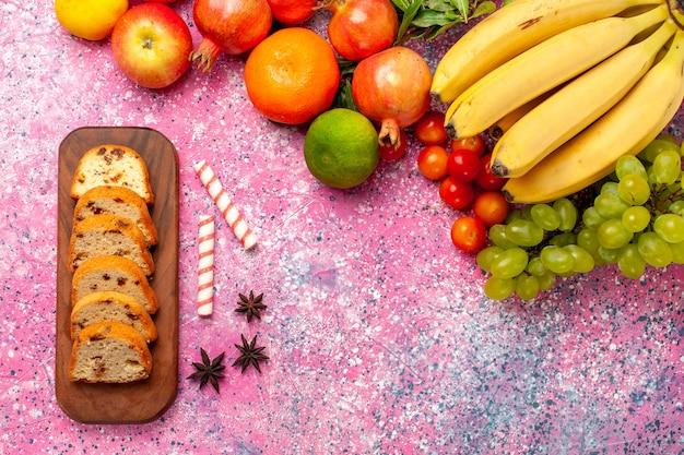 ピンクの机の上にスライスしたケーキとトップビューのおいしい果物の組成物