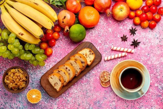 ピンクの机の上にお茶とスライスしたケーキとトップビューのおいしい果物の組成物