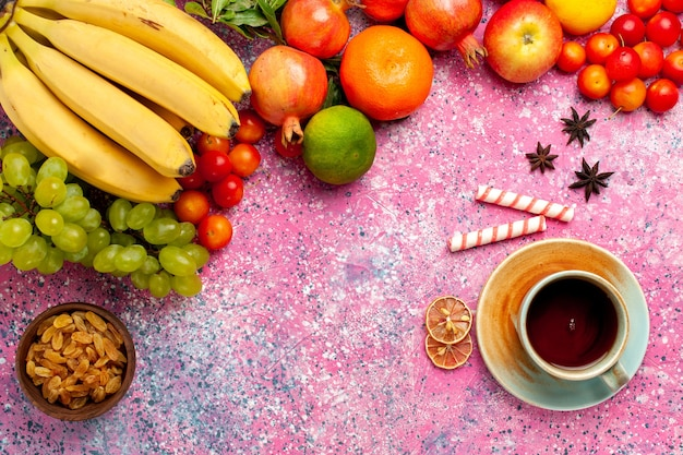 ピンクの机の上にお茶とトップビューおいしいフルーツ組成物
