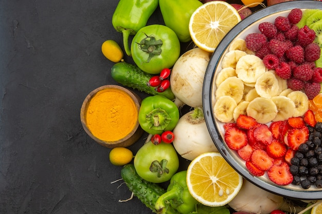 Вид сверху вкусный фруктовый салат внутри тарелки со свежими фруктами на сером тропическом фруктовом дереве экзотическая спелая диета фото