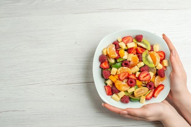 Вид сверху вкусный фруктовый салат нарезанные фрукты внутри тарелки на белом цвете здоровый образ жизни фото фрукты спелые спелые
