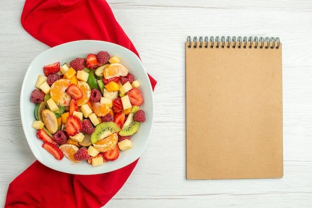 Vista dall'alto deliziosa macedonia di frutta con tessuto rosso su una foto dolce matura di bacche fruttate esotiche di agrumi bianchi