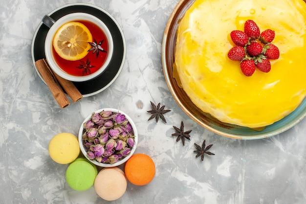 Vista dall'alto deliziosa torta fruttata con sciroppo giallo e tazza di tè sulla superficie bianca torta biscotto zucchero dolce cuocere i biscotti del tè