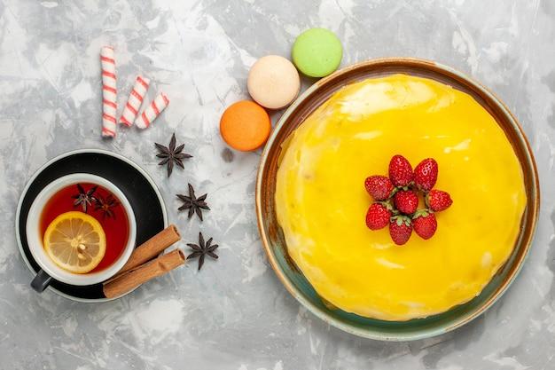 Вид сверху вкусный фруктовый торт с макаронами из желтого сиропа и чашкой чая на белой поверхности торт бисквит сладкий сахар испечь чайное печенье