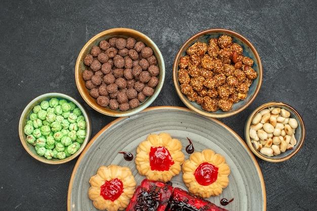 Вид сверху вкусные фруктовые торты с печеньем и конфетами на темном фоне пирог с сахарным печеньем, бисквит, сладкий чайный торт