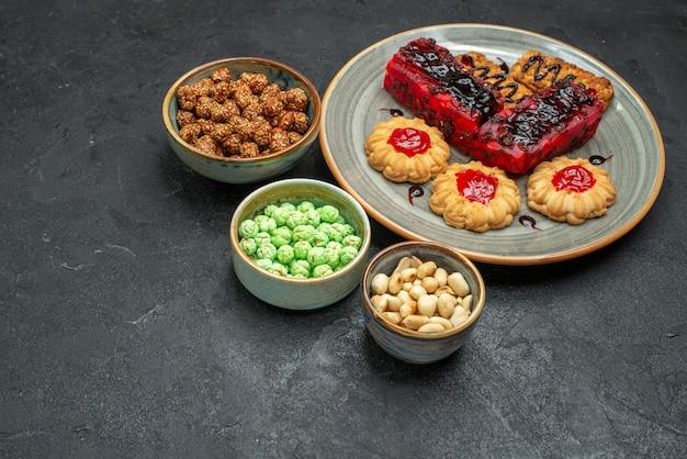 Vista dall'alto deliziose torte fruttate con biscotti e caramelle su uno sfondo scuro zucchero biscotto torta torta biscotto tè dolce