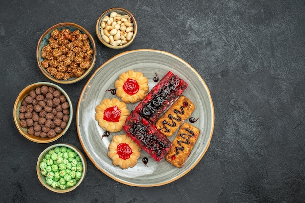 Top view delicious fruity cakes with cookies and candies on dark background sugar cookies cake pie tea biscuit sweet