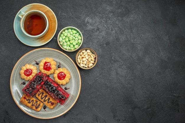 Vista dall'alto deliziose torte fruttate con biscotti e tazza di tè sullo sfondo scuro torta di biscotto di zucchero biscotto torta di tè dolce