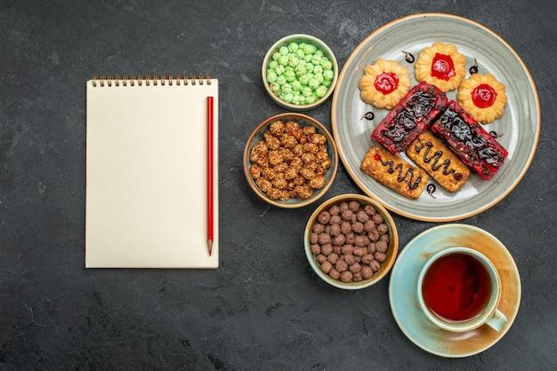 Vista dall'alto deliziose torte fruttate con biscotti e tazza di tè su sfondo grigio scuro torta di biscotto di zucchero biscotto torta di tè dolce