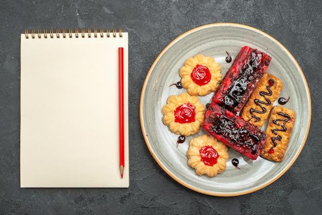 灰色の机の上のクッキーとおいしいフルーティーなケーキの上面図ビスケットケーキクッキークッキー甘い