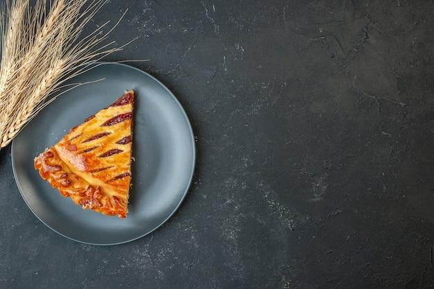 Vista dall'alto deliziosa fetta di torta fruttata con marmellata all'interno del piatto sul tavolo scuro