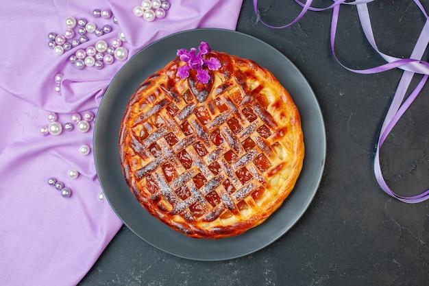 Vista dall'alto deliziosa torta alla frutta con marmellata all'interno del piatto sul tavolo scuro