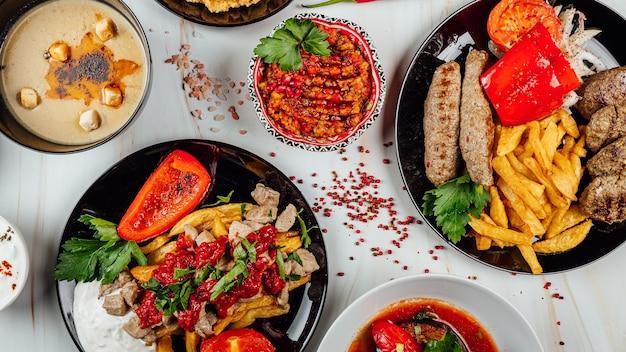 Vista dall'alto di deliziosi piatti gourmet con diverse verdure e carne