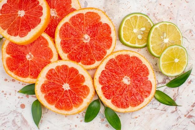Вид сверху вкусные грейпфруты, ломтики лимона на обнаженном столе