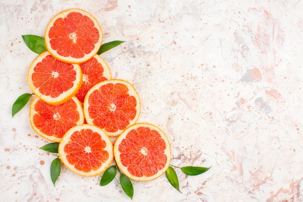 Top view delicious grapefruits slices on nude table with free place