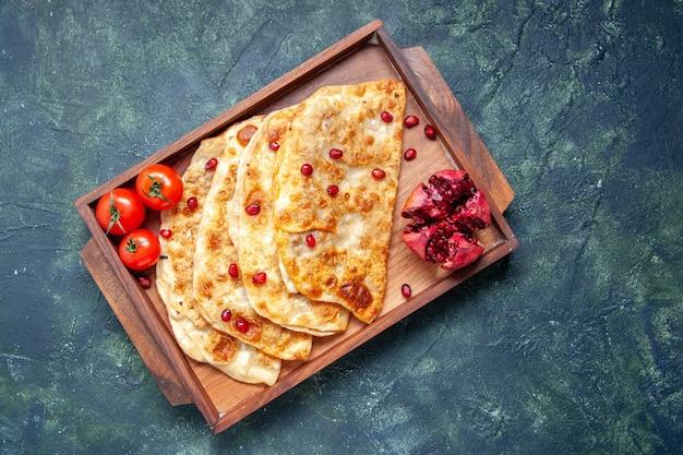 Вид сверху вкусные гутабы, тонкие горячие пирожки с мясом внутри стола на темной поверхности