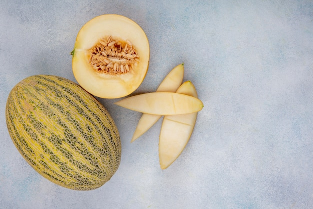 Top view of delicious halved and whole cantaloupe melon with peels on white with copy space