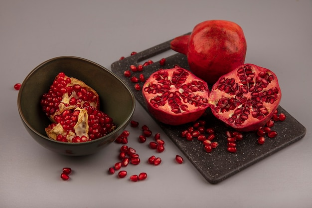 Top view of delicious halved and whole pomegranates on a black kitchen board with open pomegranates on a bowl