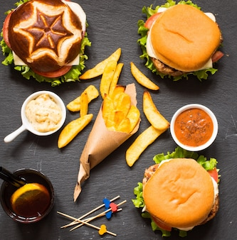 Top view of delicious hamburger, with vegetables,  on a wooden background.