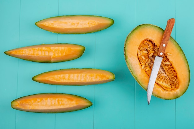 Top view of delicious healthy and fresh cantaloupe melon slices on blue