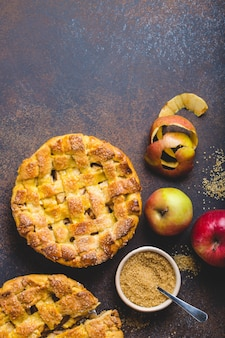 Top view of delicious homemade apple pie with cut slice, fresh apples, peel, cane sugar on brown rustic stone background. autumn or thanksgiving concept, baked apple pie for dessert, space for text